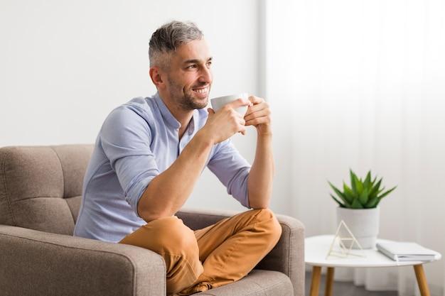 Homem de camisa azul, segurando uma xícara branca e sorrisos