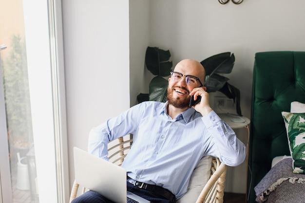 Homem de camisa azul sentado em casa com um laptop, falando ao telefone e rindo