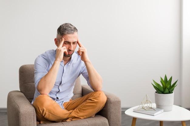 Homem de camisa azul, sentado na cadeira e pensando