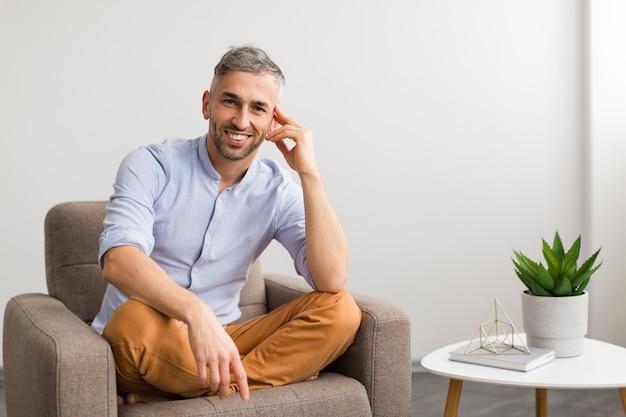 Homem de camisa azul, sentado na cadeira e sorrisos