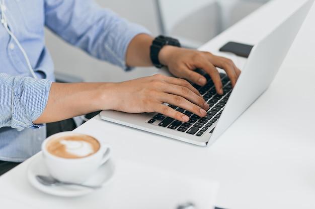 Homem de camisa azul usando laptop para trabalhar, digitando no teclado. retrato interior de mãos masculinas no computador e a xícara de café na mesa.