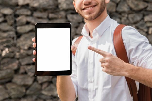 Homem de camisa branca, apontando para o seu tablet