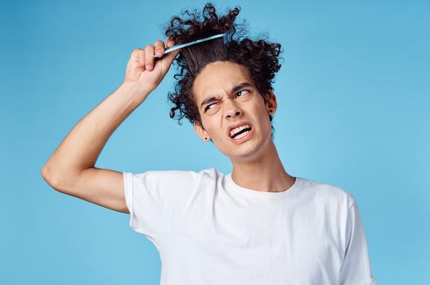 Homem de camisa branca, cabelo encaracolado preso, pentear emoções