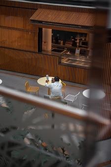 Homem de camisa branca de manga comprida sentado na cadeira no café