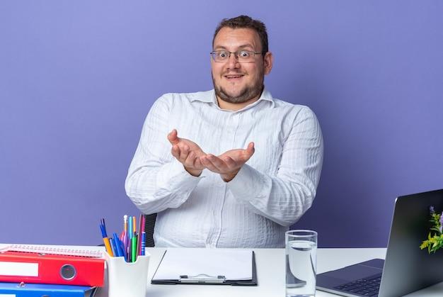 Homem de camisa branca de óculos feliz e surpreso com os braços abertos, sorrindo alegremente sentado à mesa com laptop e pastas de escritório em azul