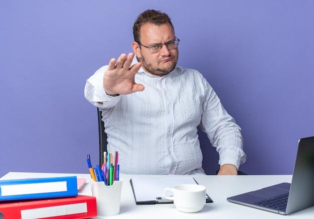 Homem de camisa branca de óculos, olhando com o rosto carrancudo, fazendo gesto de parada com a mão, sentado à mesa com laptop e pastas de escritório sobre fundo azul, trabalhando no escritório
