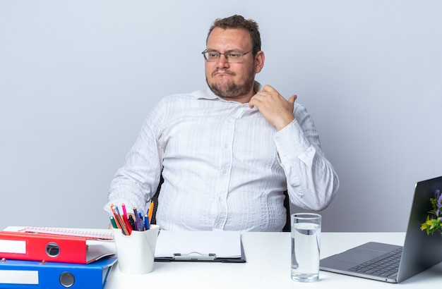Homem de camisa branca de óculos olhando de lado irritado e irritado tocando seu colarinho sentado à mesa com pastas de escritório do laptop e prancheta em branco