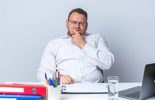 Homem de camisa branca de óculos, olhando de lado perplexo, sentado à mesa com pastas do laptop e prancheta sobre fundo branco, trabalhando no escritório