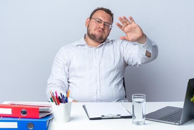 Homem de camisa branca de óculos, olhando para a frente com uma cara séria, acenando com a mão, sentado à mesa com pastas de escritório do laptop e prancheta sobre a parede branca, trabalhando no escritório