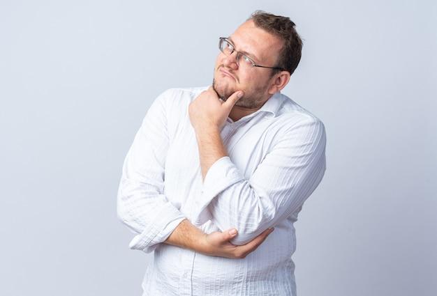 Homem de camisa branca de óculos olhando para o lado com a mão no queixo pensando em pé sobre uma parede branca