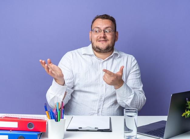Homem de camisa branca de óculos olhando para o lado com um sorriso no rosto apontando com o dedo indicador para o lado sentado à mesa com laptop e pastas de escritório sobre a parede azul trabalhando no escritório