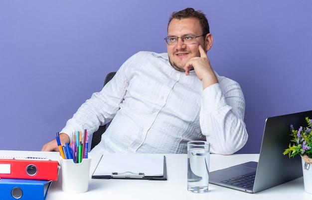 Homem de camisa branca de óculos olhando para o lado, sorrindo, confiante, pensando positivo, sentado à mesa com laptop e pastas de escritório, sobre a parede azul, trabalhando no escritório