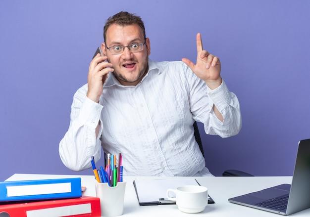 Homem de camisa branca de óculos, parecendo surpreso ao falar no celular, sentado à mesa com laptop e pastas de escritório em azul