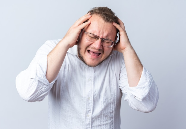 Homem de camisa branca de óculos puxando o cabelo e gritando