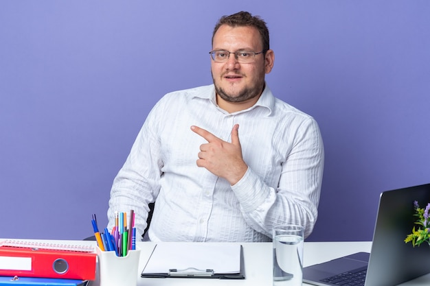 Homem de camisa branca de óculos sorrindo confiante apontando com o dedo indicador para o lado sentado à mesa com laptop e pastas de escritório sobre a parede azul trabalhando no escritório