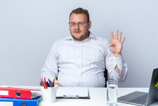 Homem de camisa branca de óculos, sorrindo, mostrando o número quatro sentado à mesa com pastas de escritório do laptop e prancheta em branco