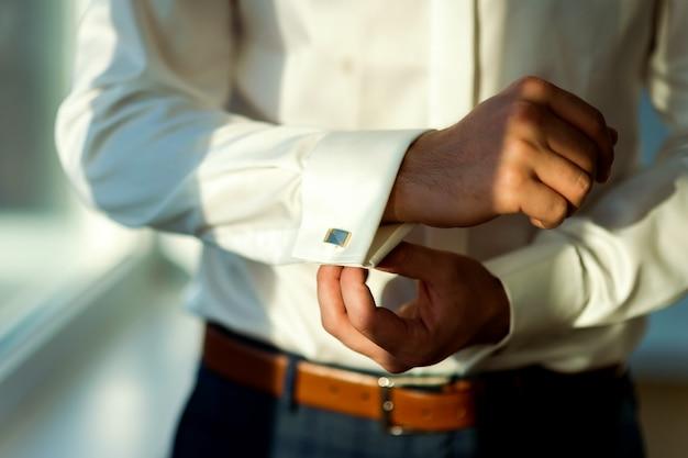 Homem de camisa branca e botão de punho
