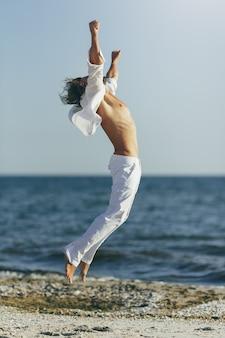 Homem de camisa branca e calça levantando as mãos na praia
