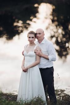 Homem de camisa branca e calça preta com uma mulher de vestido branco longo