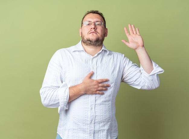 Homem de camisa branca e óculos, fazendo um juramento, levantando a mão com a outra mão no peito e rosto sério em pé sobre a parede verde