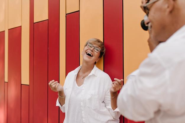 Homem de camisa branca elegante, fotografando uma mulher loira alegre com óculos na blusa clara em vermelho e laranja.