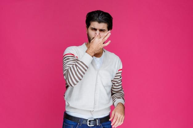 Homem de camisa branca fazendo sinal para cheirar mal e coloca o nariz.