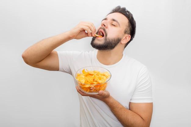 Homem de camisa branca fica e come batatas fritas. ele coloca na boca com a mão. também cara tem uma tigela com eles em outra mão. está delicioso.