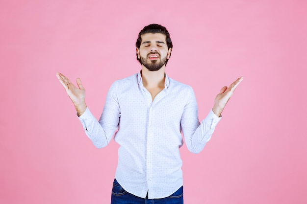 Homem de camisa branca, levantando a mão para chamar a atenção ou mostrar algo.