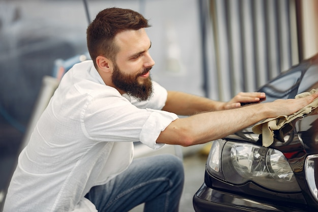 Homem de camisa branca limpa um carro em uma lavagem de carro