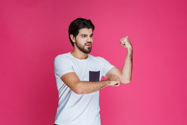 Homem de camisa branca, mostrando os músculos do punho e bíceps.