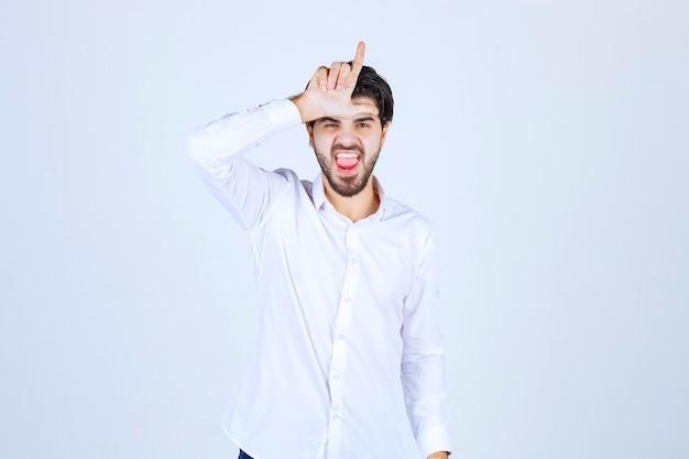 Homem de camisa branca, mostrando sinal de perdedor.