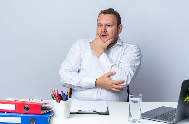 Homem de camisa branca olhando para o lado com uma expressão pensativa com a mão no queixo sentado à mesa com pastas de escritório do laptop e prancheta sobre a parede branca trabalhando no escritório
