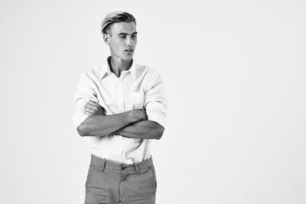 Homem de camisa branca posando com foto em preto e branco