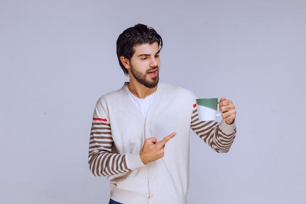 Homem de camisa branca, segurando uma caneca de café e mostrando-a.
