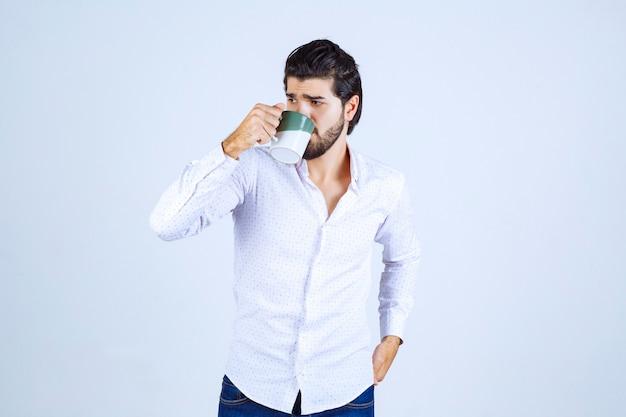 Homem de camisa branca segurando uma xícara de café e bebendo