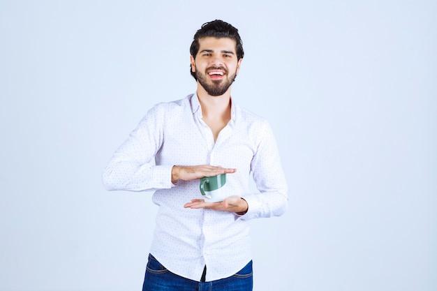 Homem de camisa branca segurando uma xícara de café e gostando