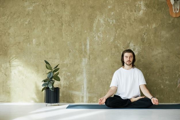 Homem de camisa branca sentado em pose de ioga e meditando, espaço de cópia, conceito de atenção plena