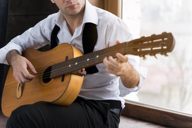 Homem de camisa branca, tocando violão dentro de casa