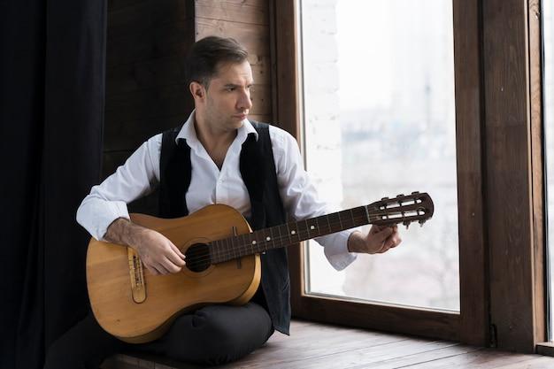 Homem de camisa branca, tocando violão em sua casa