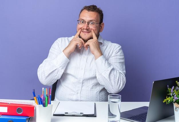 Homem de camisa branca usando óculos apontando com o dedo indicador para seu sorriso falso, sentado à mesa com laptop e pastas de escritório sobre a parede azul, trabalhando no escritório