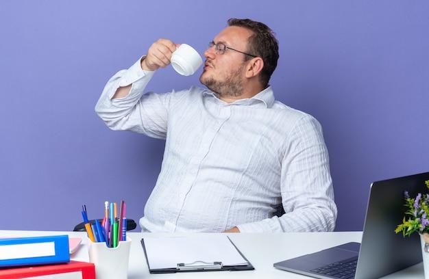 Homem de camisa branca usando óculos, bebendo chá, parecendo confiante sentado à mesa com laptop e pastas de escritório em azul
