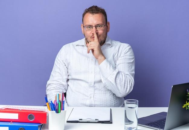 Homem de camisa branca usando óculos fazendo gesto de silêncio com o dedo nos lábios, sentado à mesa com laptop e pastas de escritório sobre a parede azul, trabalhando no escritório
