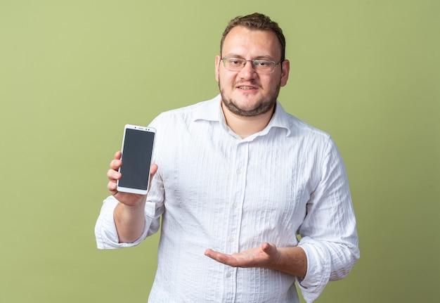 Homem de camisa branca usando óculos, mostrando o smartphone, apresentando-o com o braço da mão sorrindo confiante em pé sobre a parede verde