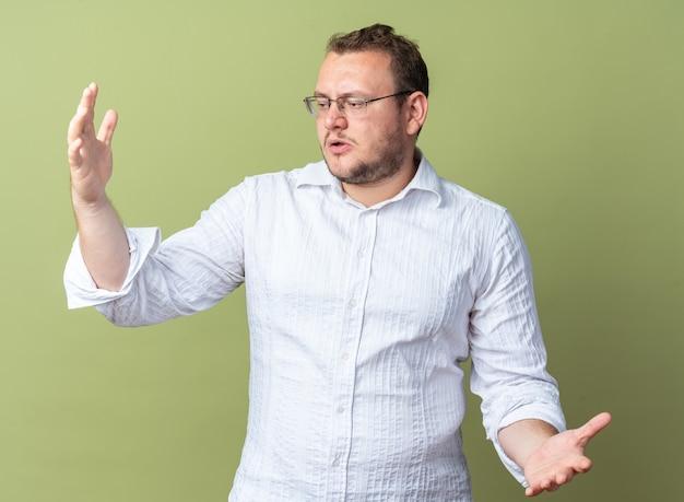 Homem de camisa branca usando óculos, olhando de lado, confuso, gesticulando com as mãos em pé sobre a parede verde