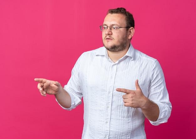 Homem de camisa branca usando óculos, olhando para o lado com uma cara séria apontando com os dedos indicadores para o lado em pé sobre a parede rosa