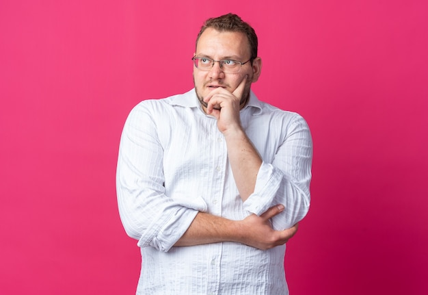 Homem de camisa branca usando óculos olhando para o lado com uma expressão pensativa no rosto pensando em pé sobre a parede rosa