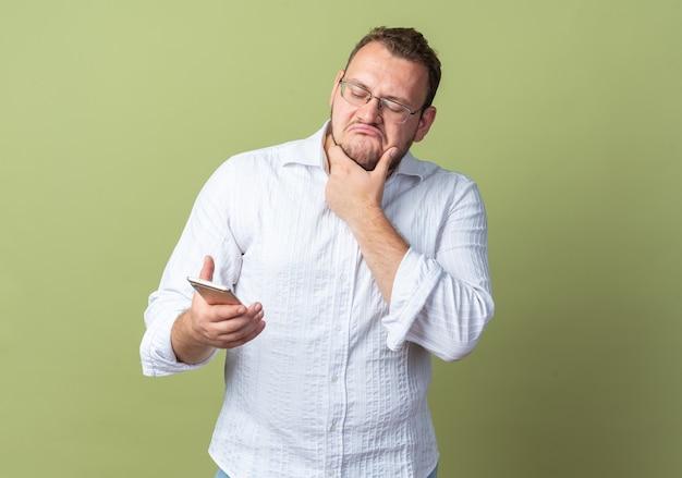 Homem de camisa branca usando óculos segurando um smartphone olhando para ele com expressão cética em pé sobre uma parede verde