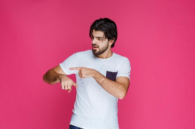 Homem de camisa branca, verificando as horas no relógio.