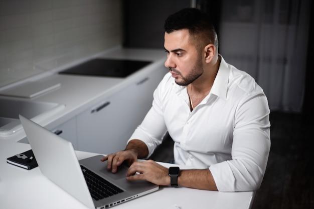 Homem de camisa branca websurfing com o laptop na cozinha de casa