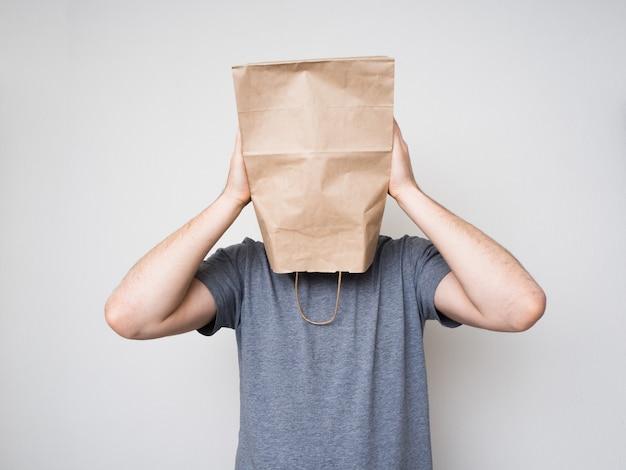 Homem de camisa cinza e um saco de papel na cabeça.